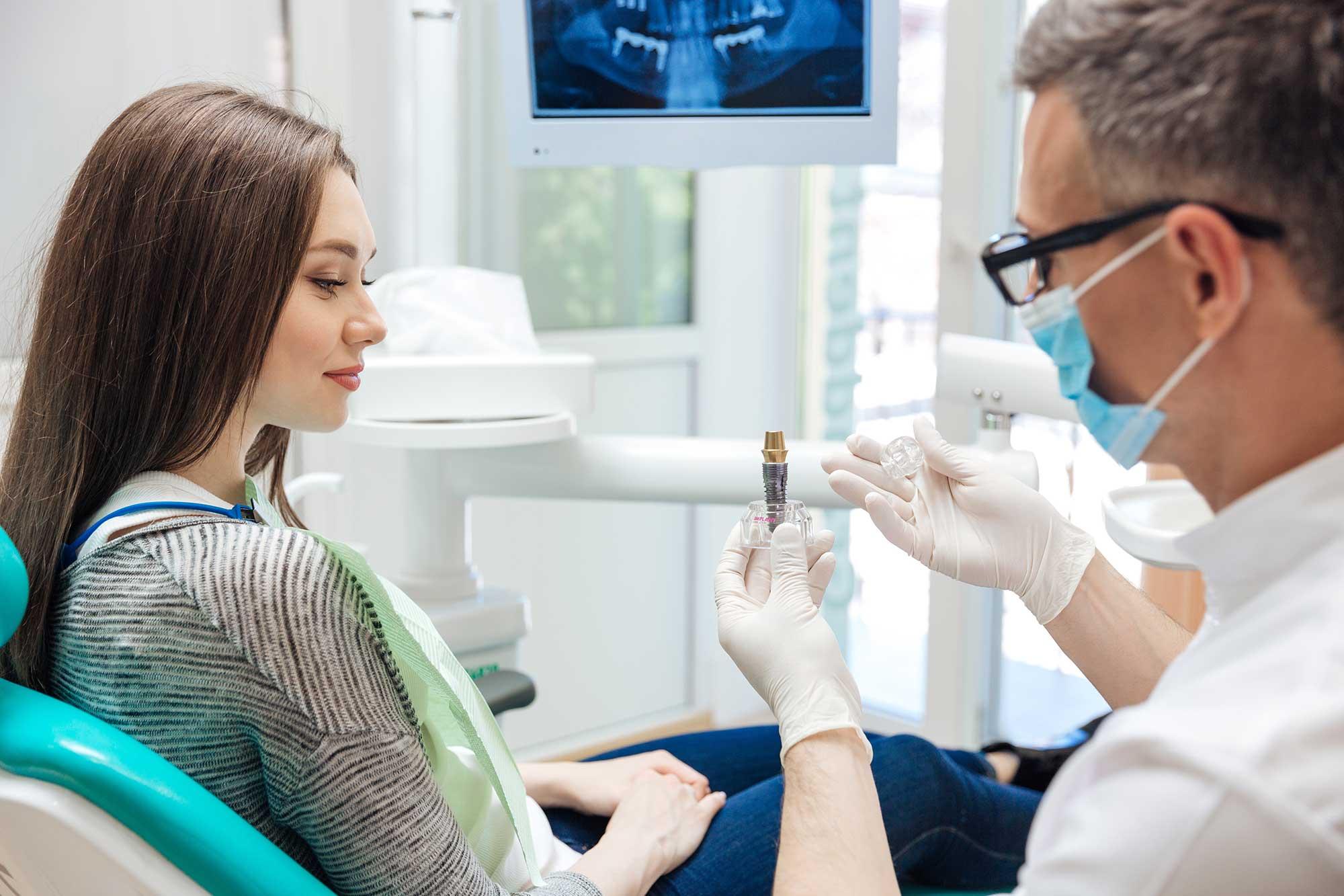Zahnarzt berät Patientin zum Implantat